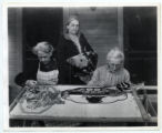 Three women making hooked rugs