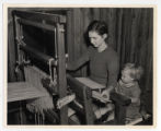 A woman and child seated at a loom