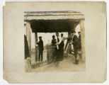 Men standing beneath a shelter at a well