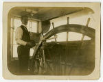 Man standing at pilot's wheel on steamboat