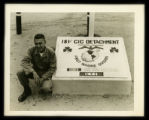 Frank Matthews kneeling at flagpole base