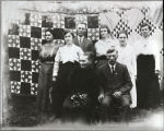 Rupper family posing in front of two quilts